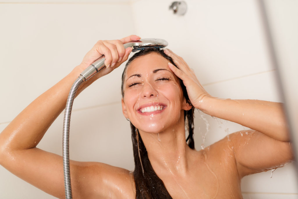 Happy young woman washing face and hair while showering under shower head.